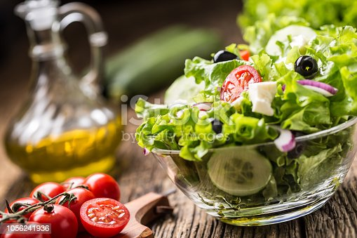 879977192 istock photo Vegetables lettuce salad with tomatoes onion cheese and olives. 1056241936