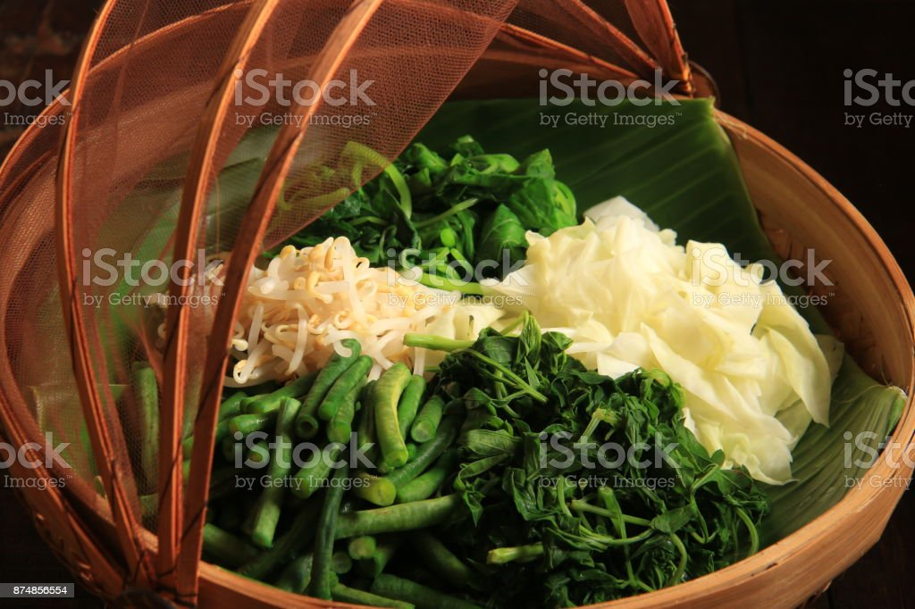 Vegetables of Pecel, the Traditional Javanese Vegetable Salad, on Bamboo Basket with Mesh Lid stock photo