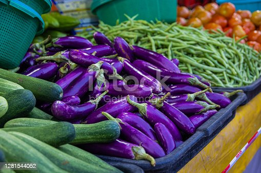 Vegetables on a counter of a vegetable shop in the fresh market. Aubergine or eggplant, beans and cucumber on the counter of the stand. The Putrajaya, Malaysia fresh market at Friday night.