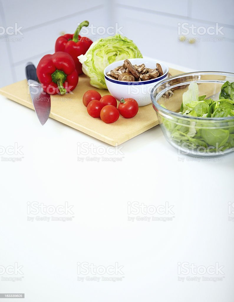 Vegetables on cutting board with a knife in the kitchen royalty-free stock photo