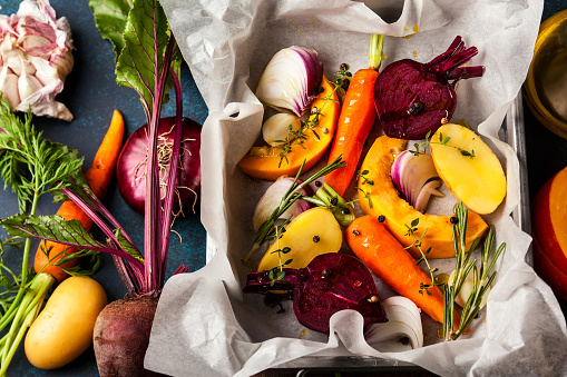 Preparing  roasted vegetables with garlic and herbs on the baking tray. Autumn-winter root vegetables.