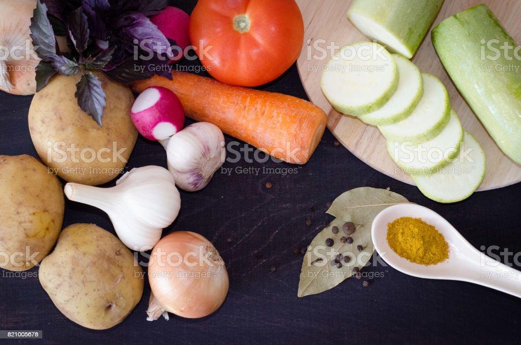vegetables potato, tomato, onion, garlic and zucchini slices and radish, spices stock photo