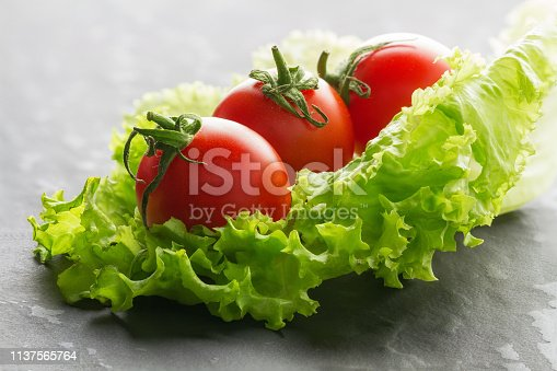 Vegetables. Salad and tomatoes closeup on a textural background. Healthy vegetarian breakfast.