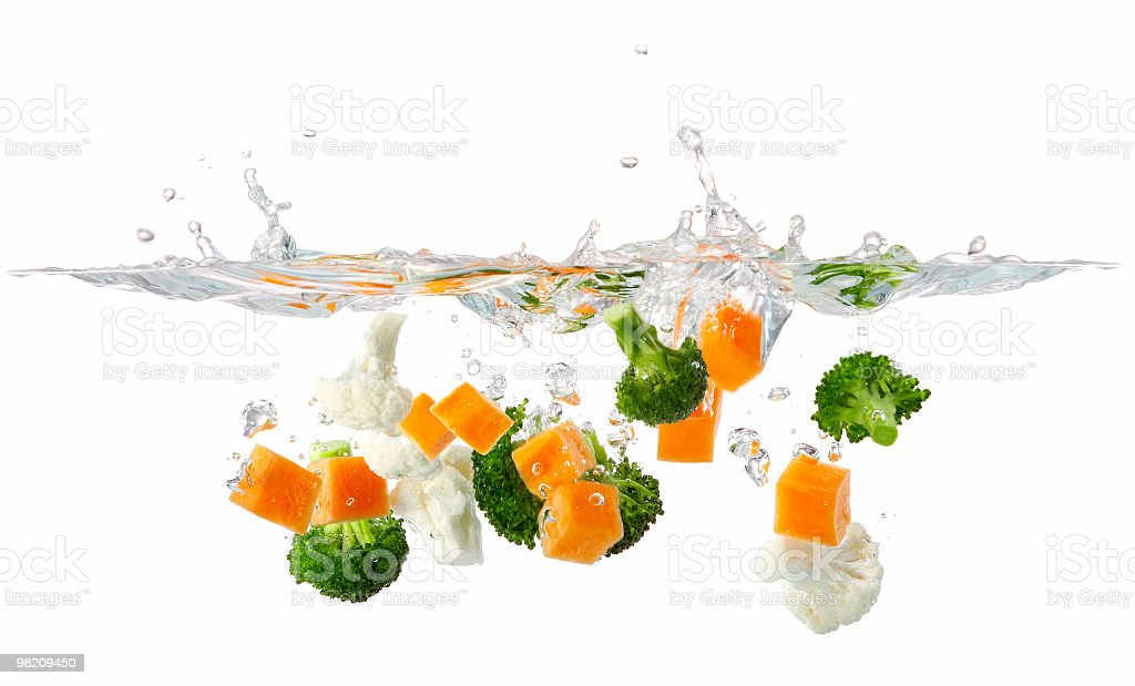 Vegetables splashing in water on white background royalty-free stock photo