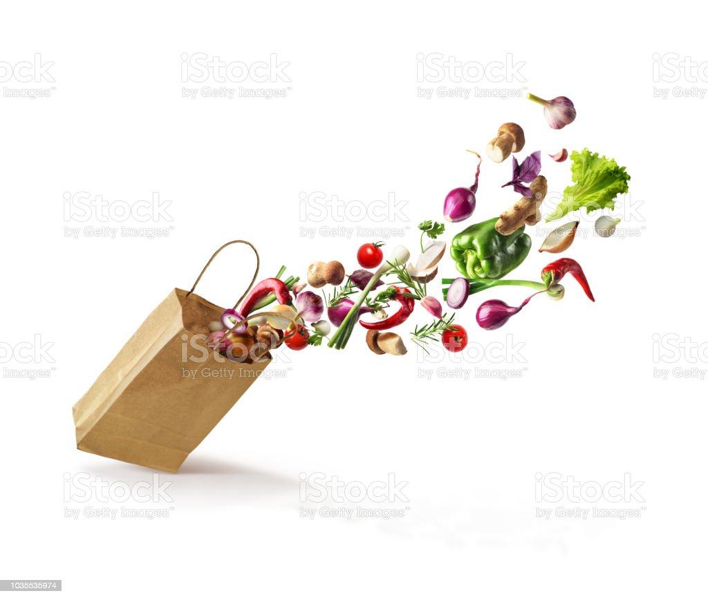 Gemüse, die aus einer Papiertüte isoliert auf einem weißen Hintergrund fliegen. Gesunde Ernährung – Foto