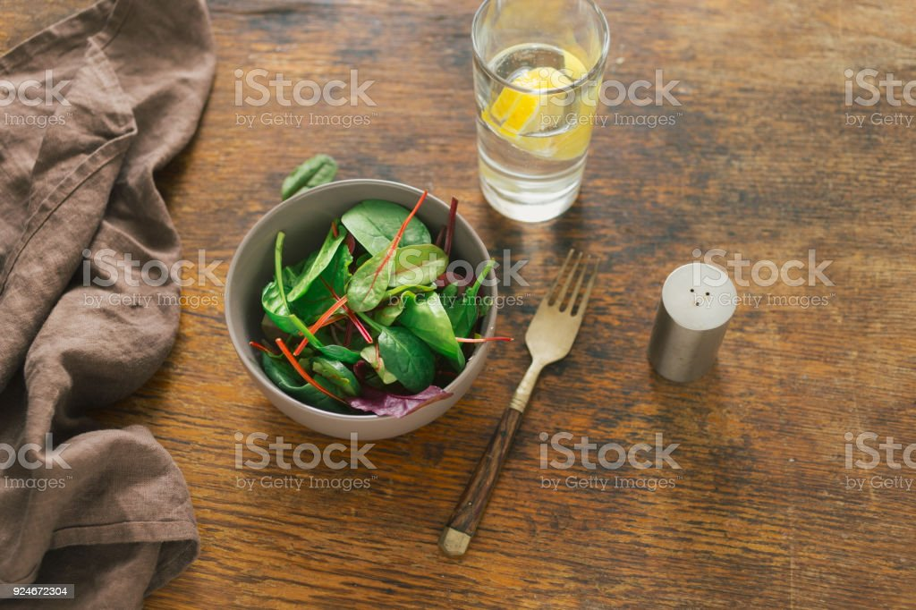 Vegetarian biodynamic food concept. Bowl of salad with spinach leaves and beet leaves on dark wooden table with glass of water with lemon. Top view - foto stock