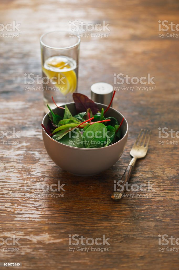 Vegetarian biodynamic food concept. Bowl of salad with spinach leaves and beet leaves on wooden table with water with lemon - foto stock