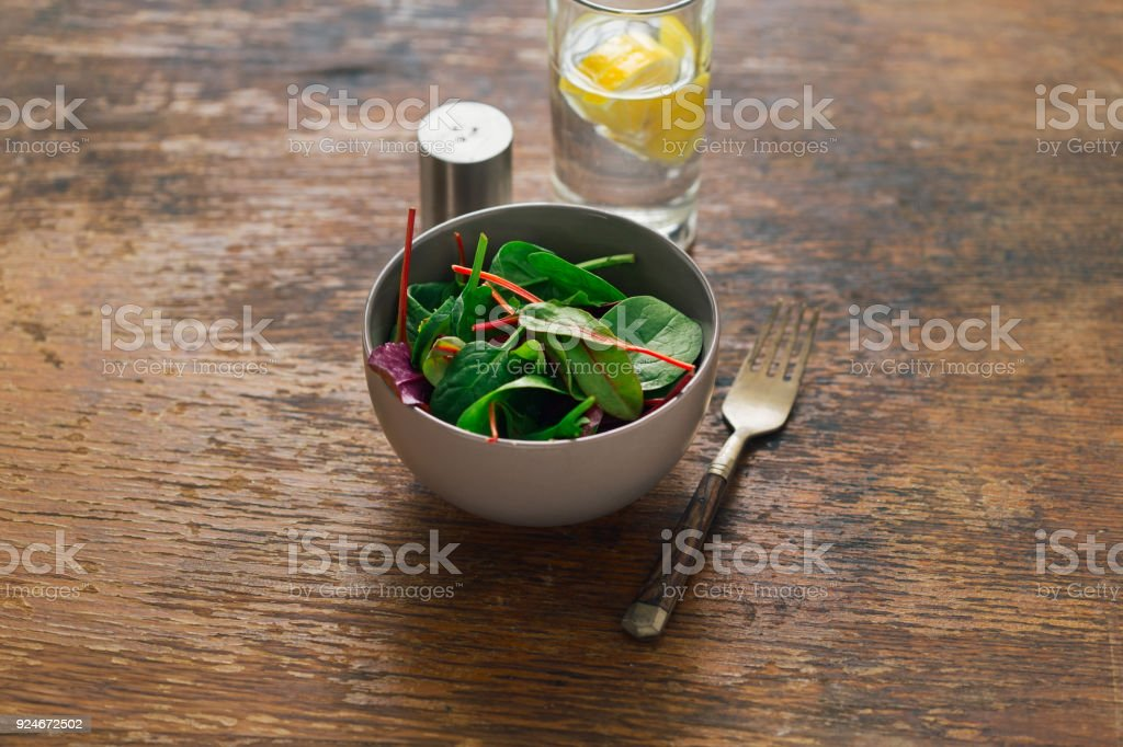 Vegetarian biodynamic food concept. Bowl of salad with spinach leaves and beet leaves on dark wooden table with water with lemon - foto stock