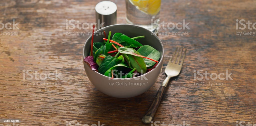 Vegetarian biodynamic food concept. Bowl of salad with spinach leaves and beet leaves on dark wooden table with glass of water with lemon - foto stock