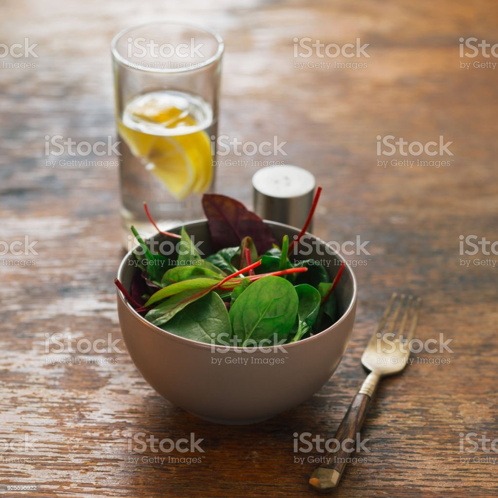 Vegetarian biodynamic food concept. Close up bowl of salad with spinach leaves and beet leaves on dark wooden table with glass of water with lemon - foto stock