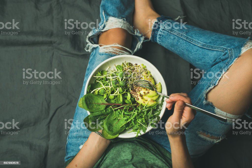 Vegetarian breakfast bowl with spinach, arugula, avocado, seeds and sprouts stock photo