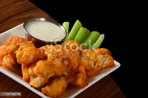 A vegetarian take on the classic Buffalo chicken wings - spicy baked cauliflower bites served with celery sticks and blue cheese dipping sauce.