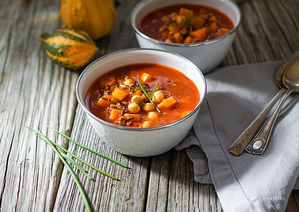 Vegetarian Chili, Posole. Vegetarian tasty spicy chili chick pea pumpkin wild rice soup pozole stew bowl on a wooden background squash vegetable stock pictures, royalty-free photos & images