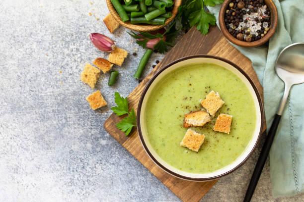 채식 요리. 밝은 배경에 녹색 콩의 식이 맛있는 크림 수프. 상단보기 평면 누워. 텍스트에 사용할 수 있는 여유 공간입니다. 스톡 사진
