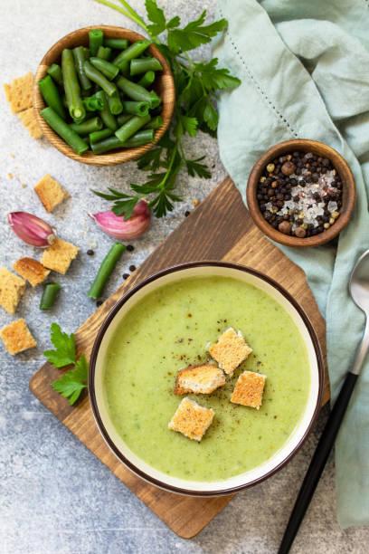 채식 요리. 밝은 배경에 녹색 콩의 식이 맛있는 크림 수프. 상단보기 평면 누워. 스톡 사진