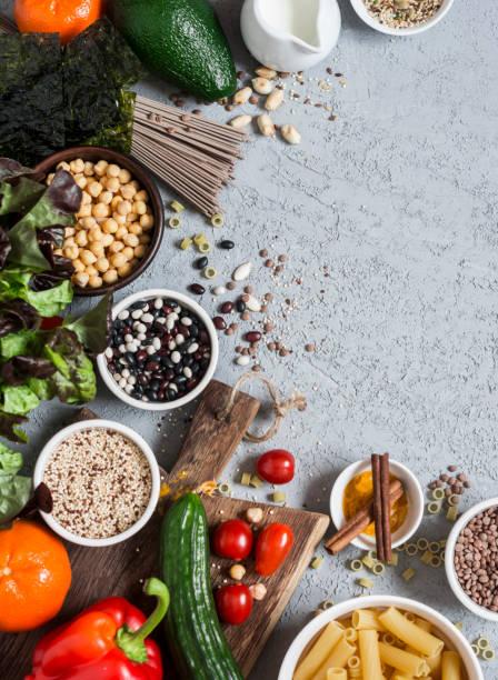 vegetarische kost hintergrund. reihe von vegetarischen produkten auf der grauen tabelle, ansicht von oben. gesunde ernährung-food-konzept. freier speicherplatz - zimt gurken stock-fotos und bilder