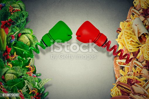 istock Vegetarian food fighting junk food with boxing gloves 613870032