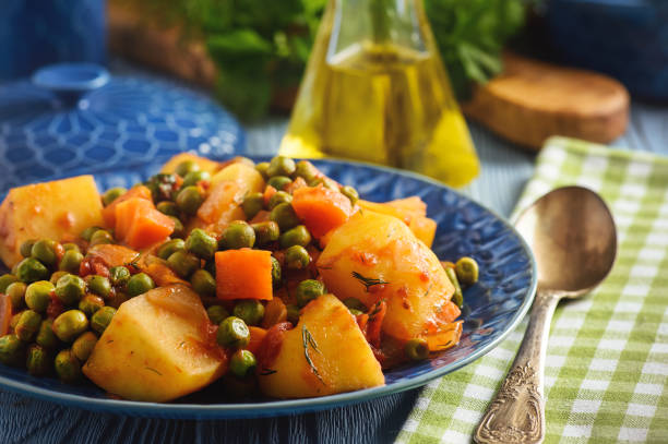 Vegetarian food - potatoes with pea and tomatoes, greek style cuisine. stock photo