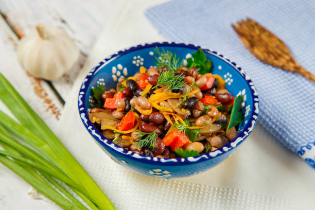 Vegetarian food, protein food, salad of three types of beans with fried mushrooms, carrots and bell pepper with herbs stock photo