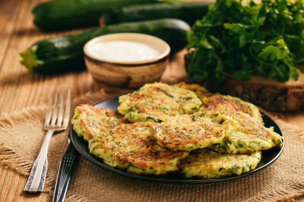 Vegetarian food - zucchini fritters on wooden background. stock photo
