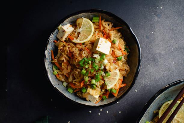 vegetarische reispfanne mit tofu, erbsen und gemüse. asiatische küche, gesundes mittagessen - hausgemachter gebratener reis stock-fotos und bilder