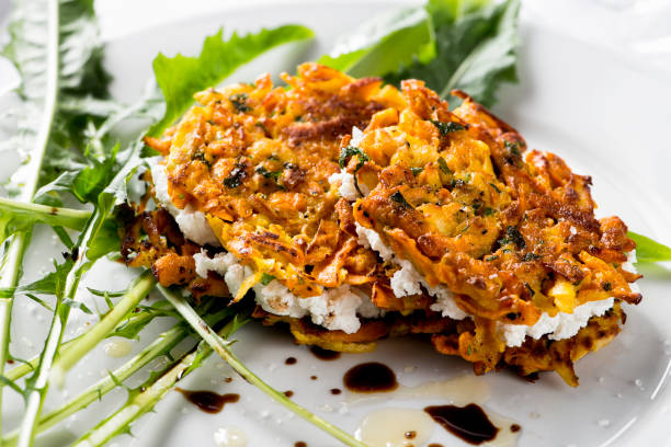 Vegetarian Fritters Sweet potato scallion fritters stuffed with goat cheese on dandelion greens with balsamic vinegar. fritter stock pictures, royalty-free photos & images