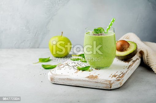 istock Vegetarian healthy green smoothie from avocado, spinach leaves, apple and chia seeds on gray concrete background. Selective focus. Space for text. 984772004