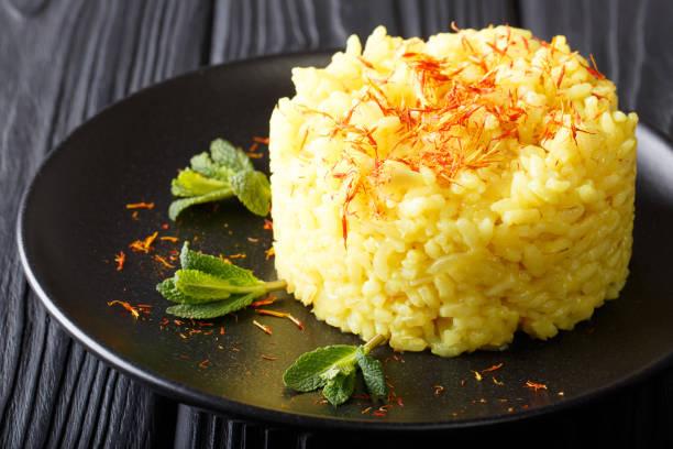 Vegetarian Italian food: risotto with saffron and mint (Risotto alla milanese) closeup. horizontal stock photo