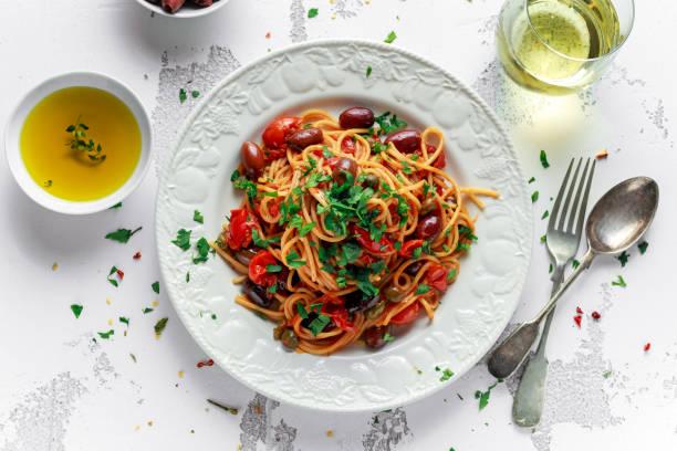 vejetaryen i̇talyan makarna alla sıpagetti sarımsak, zeytin, beyaz tabakta ile kapari - i̇talyan kültürü stok fotoğraflar ve resimler