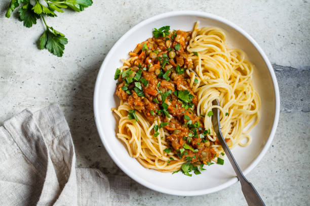 Vegetarian lentils bolognese pasta with parsley in white dish, top view. Healthy vegan food concept. Vegetarian lentils bolognese pasta with parsley in a white dish. Healthy vegan food concept. bolognese sauce stock pictures, royalty-free photos & images