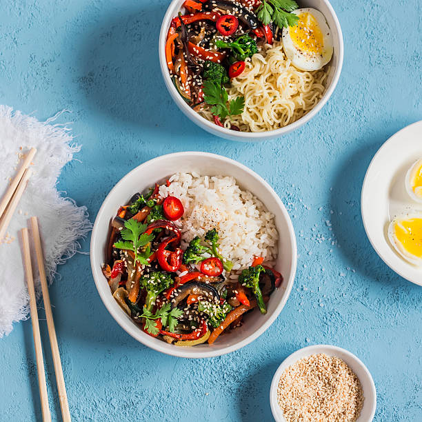 Vegetarian lunch -  bowls with rice, noodles, vegetable stir fry stock photo