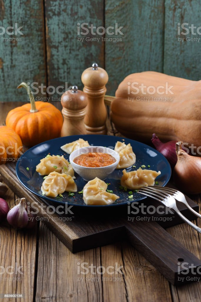 Vegetarian meal. Asian steam dumplings with curry sauce served with pumpkins and onion on rustic background stock photo