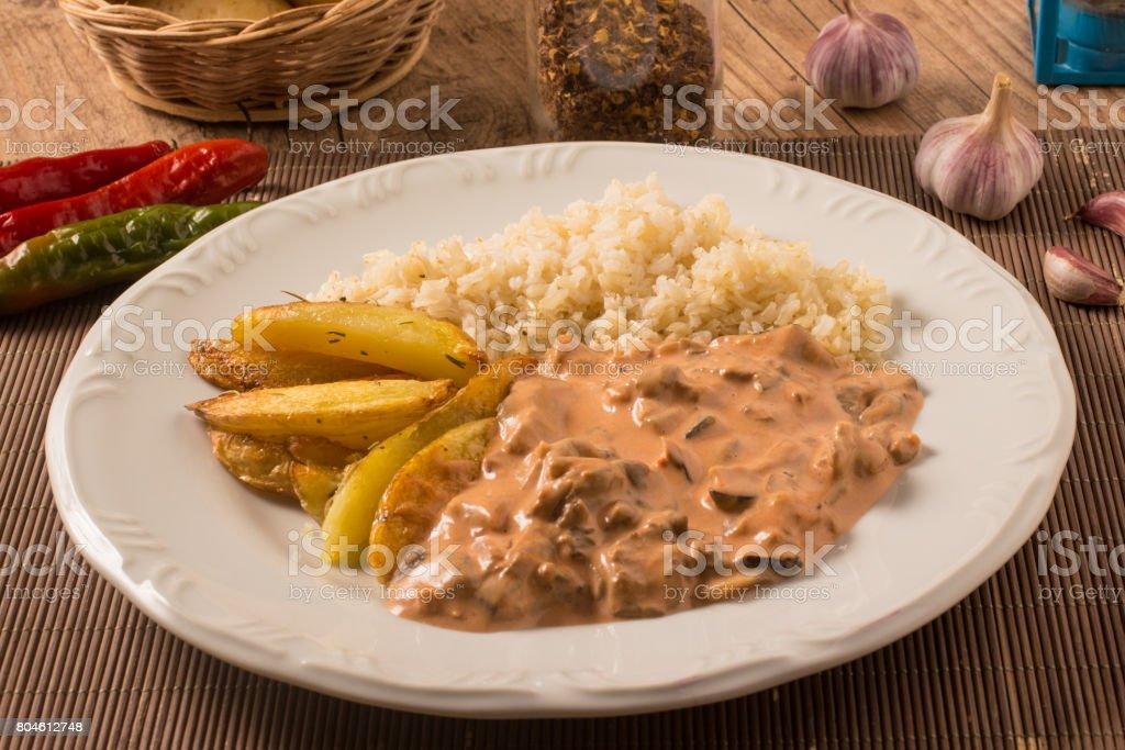 Vegetarian Mushroom Stroganoff with rice and rustic potatoes. stock photo