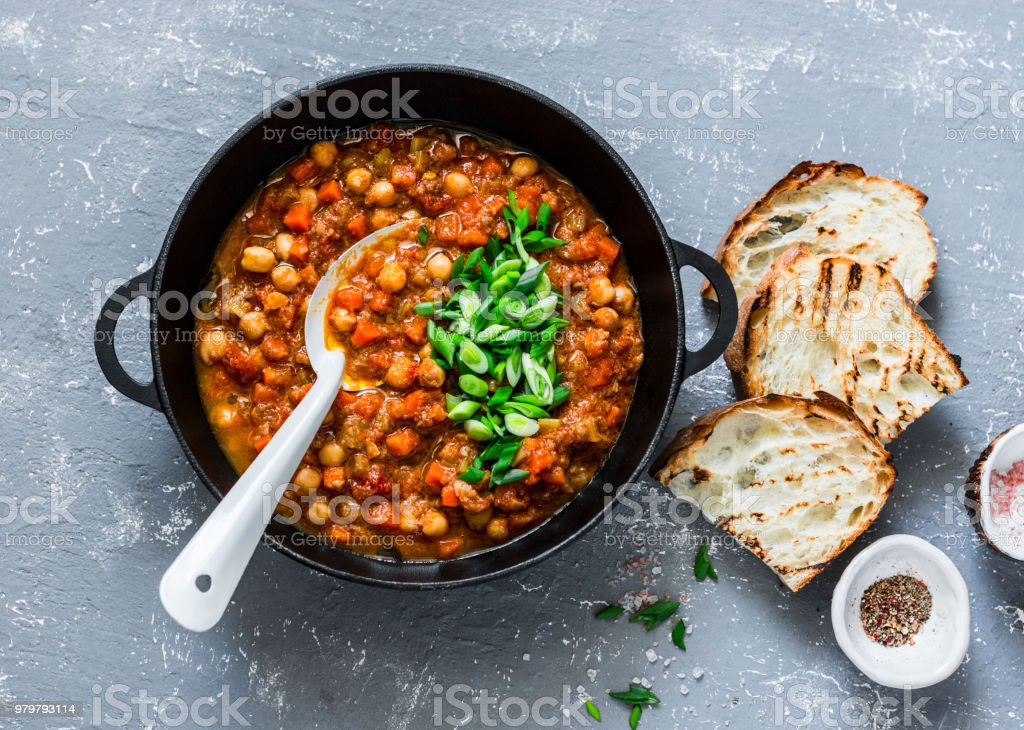 Vegetarian mushrooms chickpea stew in a iron pan and rustic grilled bread on a gray background, top view. Healthy vegetarian food concept. Vegetarian chili - Zbiór zdjęć royalty-free (Cebula)