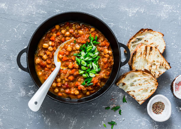 vegetarian mushrooms chickpea stew in a iron pan and rustic grilled bread on a gray background, top view. healthy vegetarian food concept. vegetarian chili - vegetariano foto e immagini stock
