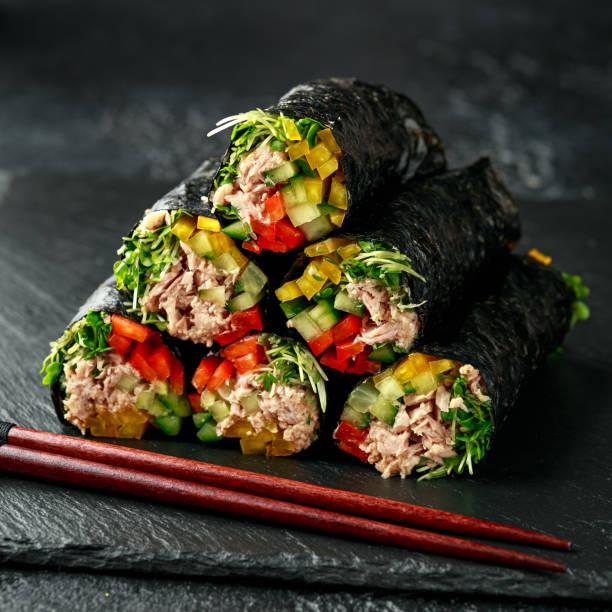 Vegetarian paleo diet nori wraps with tuna, cucumber, sweet pepper and microgreen radish sprouts stock photo