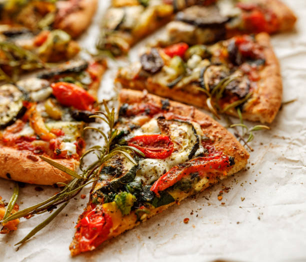 Vegetarian pizza with addition grilled vegetables and aromatic herbs Vegetarian pizza with addition grilled vegetables and aromatic herbs, divided into portions pizza stock pictures, royalty-free photos & images