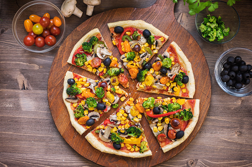 Homemade vegetarian pizza with broccoli, cherry tomato, pepper, black olives and mushrooms