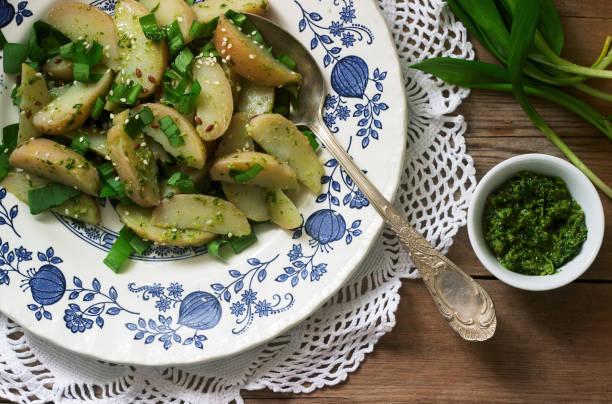 vegetarischer kartoffelsalat mit wildem knoblauch und pesto-sauce auf holzhintergrund. rustikal. - bärlauchsalz stock-fotos und bilder