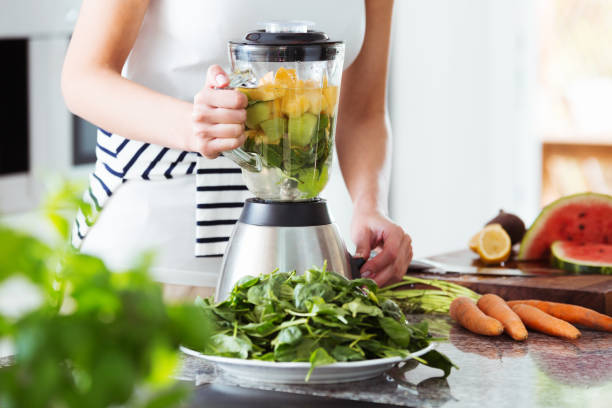 Vegetarian preparing vegan smoothie Vegetarian preparing vegan smoothie with rucola, citrus, cucumber in kitchen with carrots on countertop blender stock pictures, royalty-free photos & images