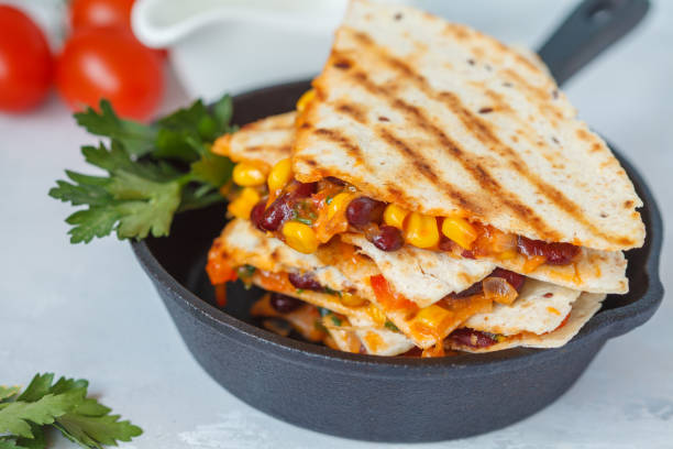 Vegetarian quesadilla with vegetables and cheese in cast iron frying pan stock photo