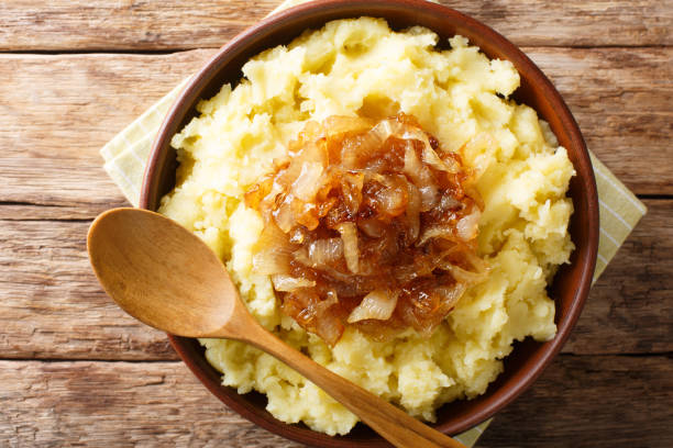 Vegetarian rustic food mashed potatoes with caramelized onions close-up on a plate on the table. Horizontal top view stock photo
