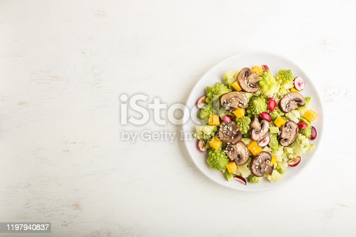 Vegetarian salad from romanesco cabbage, champignons, cranberry, avocado and pumpkin on a white wooden background and linen textile. top view, copy space, flat lay.