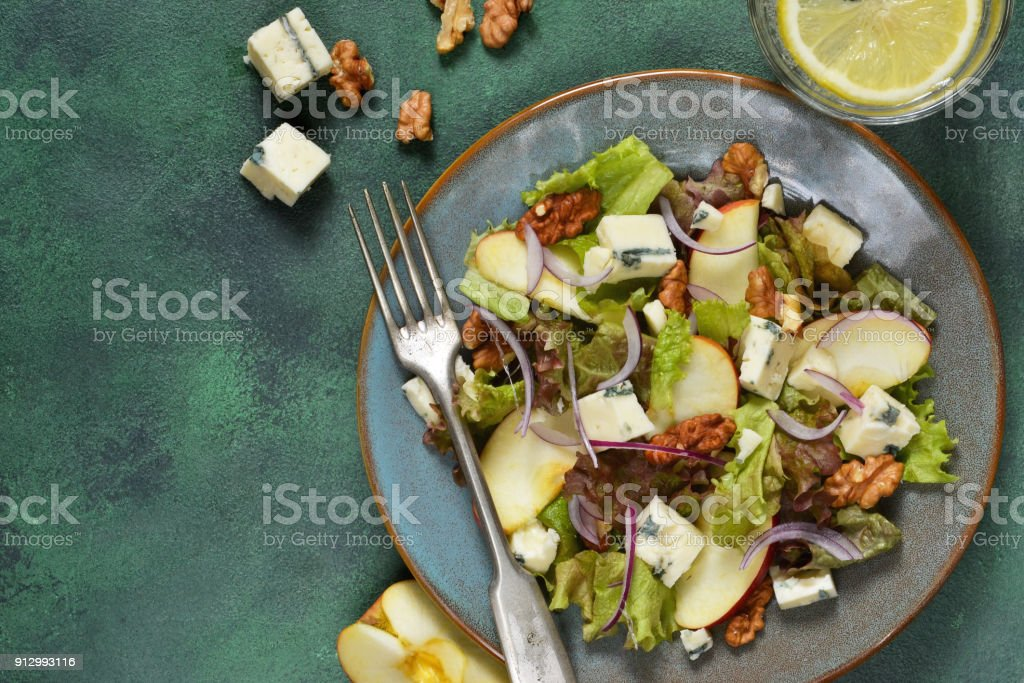 Vegetarian salad with blue cheese, apples and walnuts with mustard sauce. stock photo