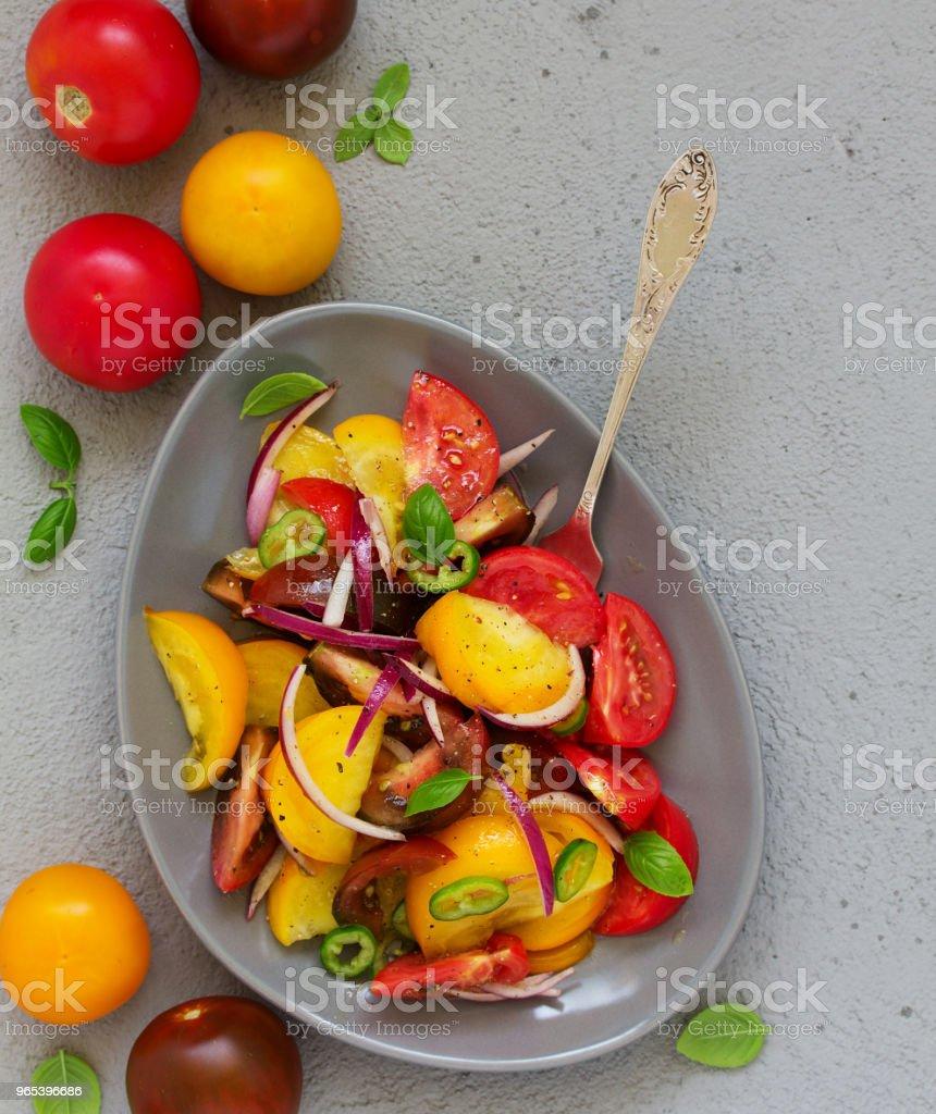 Salade végétarienne avec des tomates fraîches, oignons rouges, basilic et huile d'olive. - Photo de Assiette libre de droits
