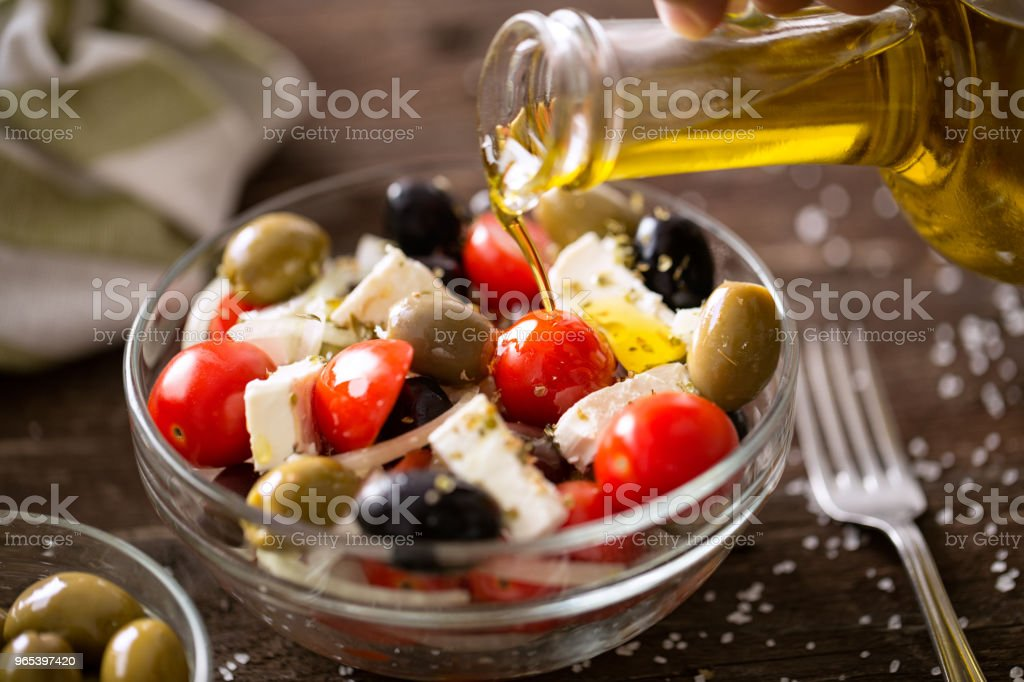 vegetarian salad with fresh vegetables, feta and green olives pouring virgin olive oil royalty-free stock photo