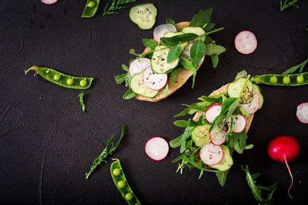 vegetarische sandwiches mit gurke, radieschen, rucola und grünen erbsen. flach zu legen. ansicht von oben - englischer erbsen salat stock-fotos und bilder
