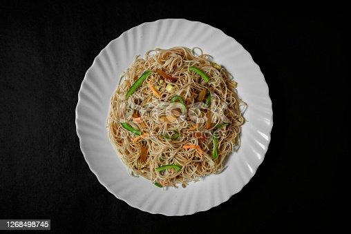 Vegetarian Schezwan Noodles or Vegetable Hakka Noodles or Chow Mein in white plate at wooden background. Schezwan Noodles is indochinese cuisine hot dish with udon noodles, vegetables and chilli sauce