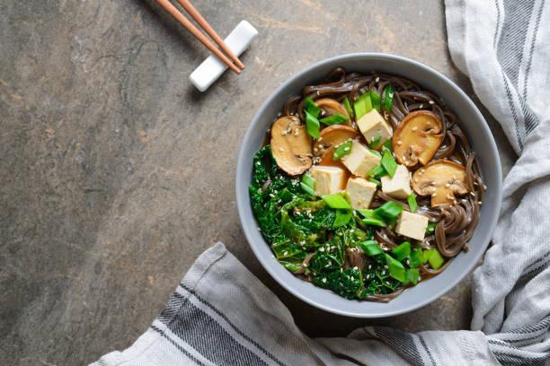 vegetarische soep met boerenkool champignons en soba noedels - sobanoedels stockfoto's en -beelden