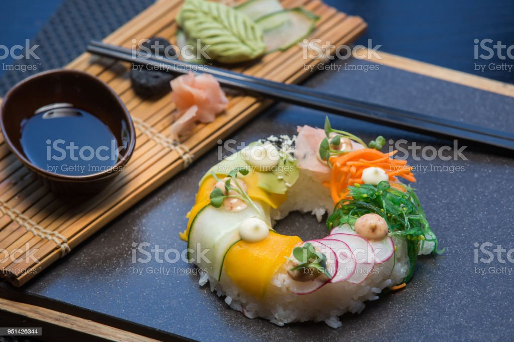 Vegetarian sushi donuts set with ginger, avocado, cucumber, chives served on stone slate. Sushi-food hybrids trend. high-end cuisine stock photo
